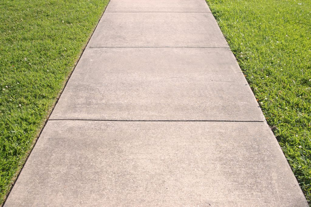 Detail of a concrete sidewalk with grass on both sides