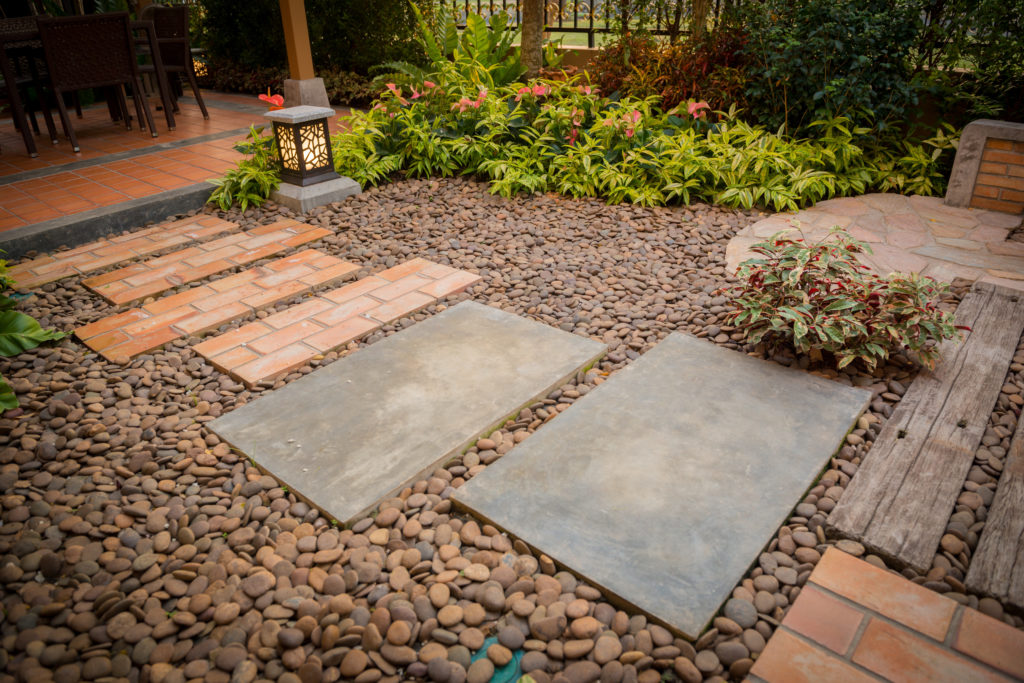 Decorative garden with pebbles and stepping stones as a pathway.