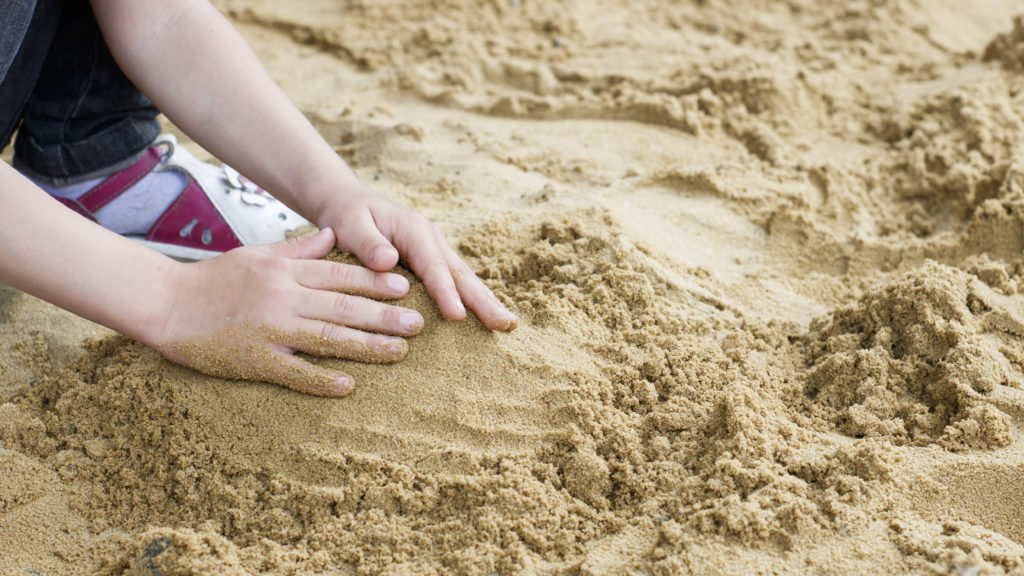 the child is building a tower of sand on the seashore