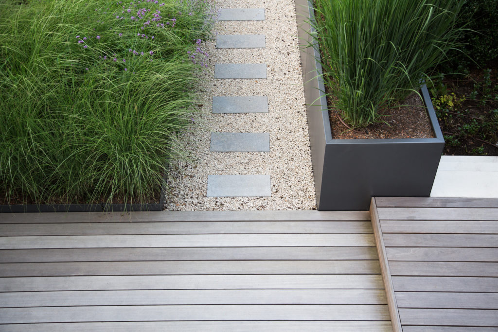 A beautiful landscaping job with grass, gravel, and wood panels