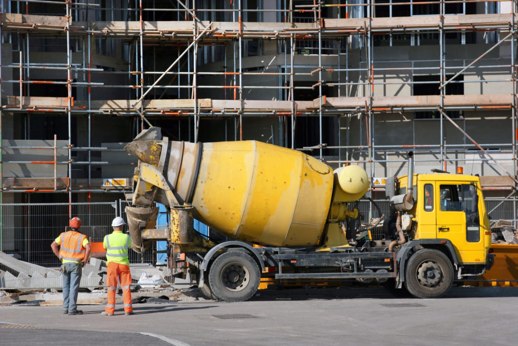 Yellow cement mixer truck parked in fornt of a new building under construction with scaffolding in position. Two workmen standing to the left hand side, rear view.